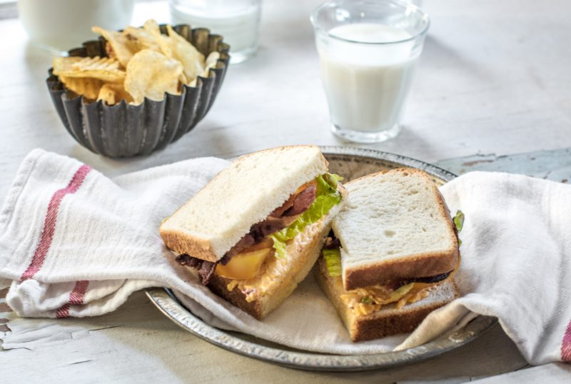 A black metal bowl with potato chip, glass of milk, and a sliced loaded BLT sandwich with Pepperidge Farm hearty white bread.