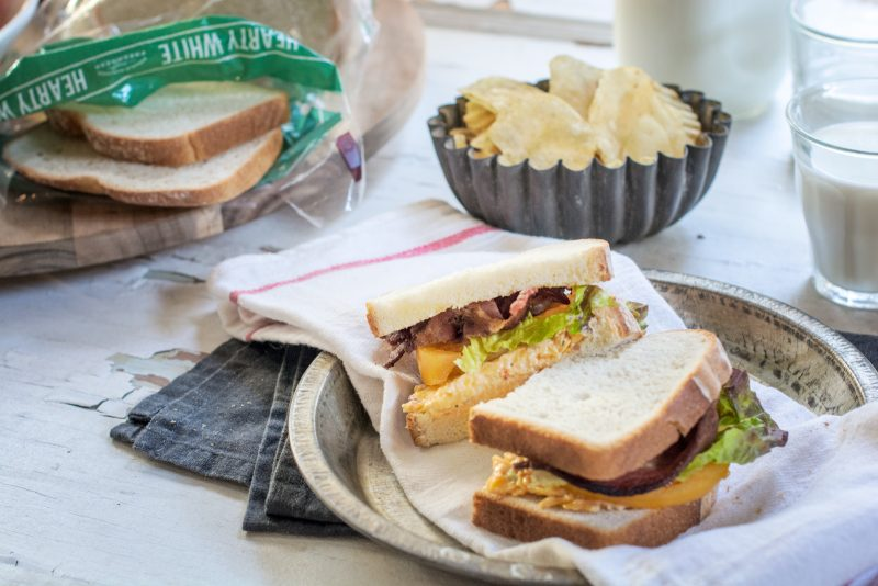 A sliced BLT sandwich with potato chips on the side and opened bag of Pepperidge Farm hearty white bread