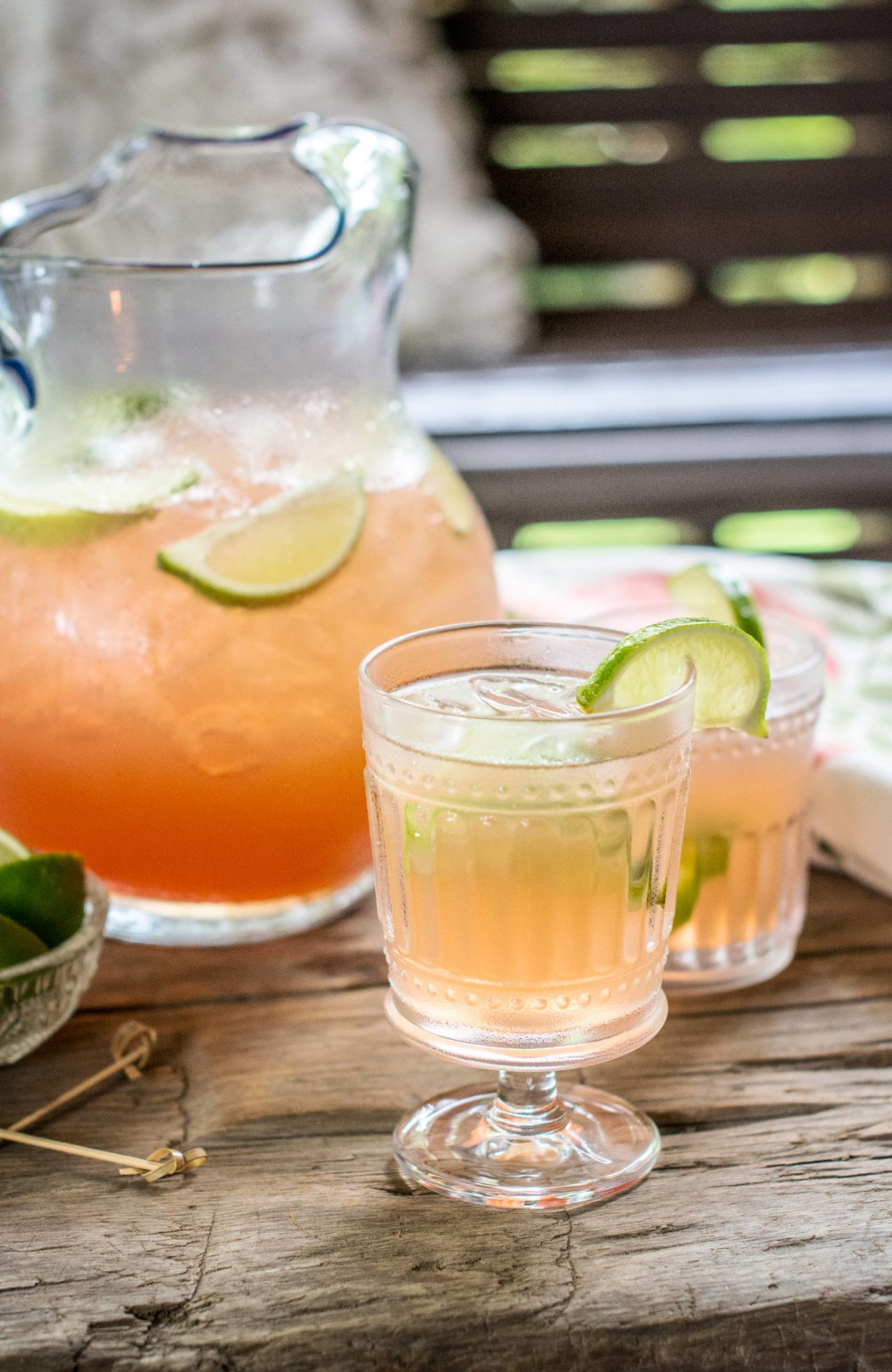 Clear glasses and pitcher filled with Scarlet O'Hara Cocktail punch and garnished with lime wedges
