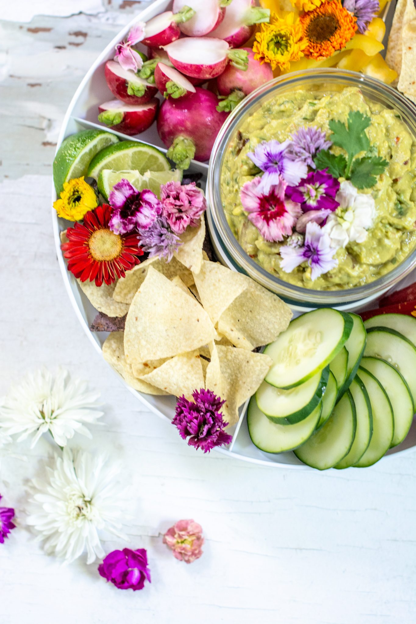Fresh sliced vegetables surrounding a bowl of spicy guacamole on a white table.
