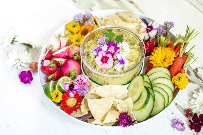 Overhead view of guacamole surrounded by fresh sliced vegetables and decorated with white and pink flowers on white background.