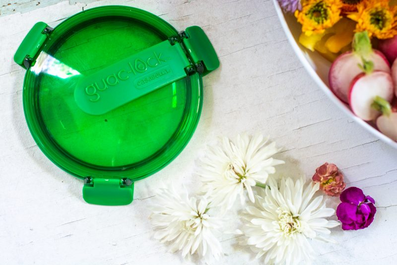 Guac Lock green lid beside white and pink flowers on a white table.