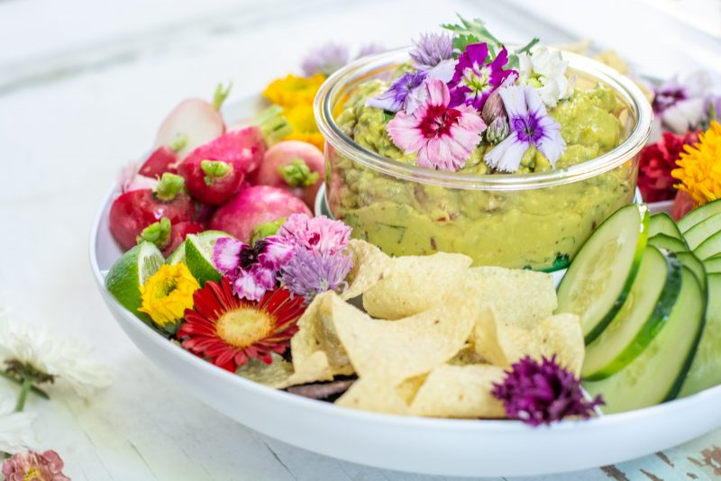 Spicy Guacamole recipe in a bowl served with fresh vegetables and tortilla chips on a white table.