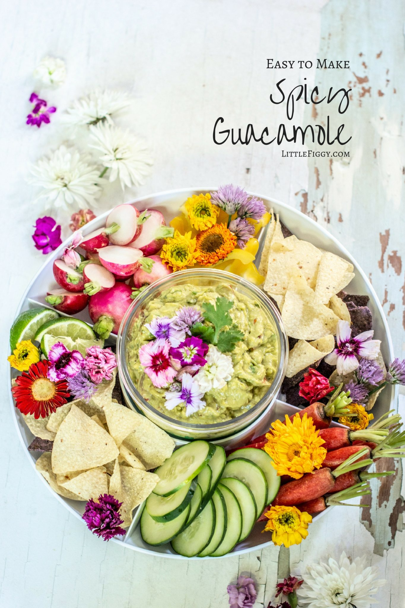 Serving dish with vegetables and spicy guacamole nested in middle of dish, decorated with pink and white flowers.