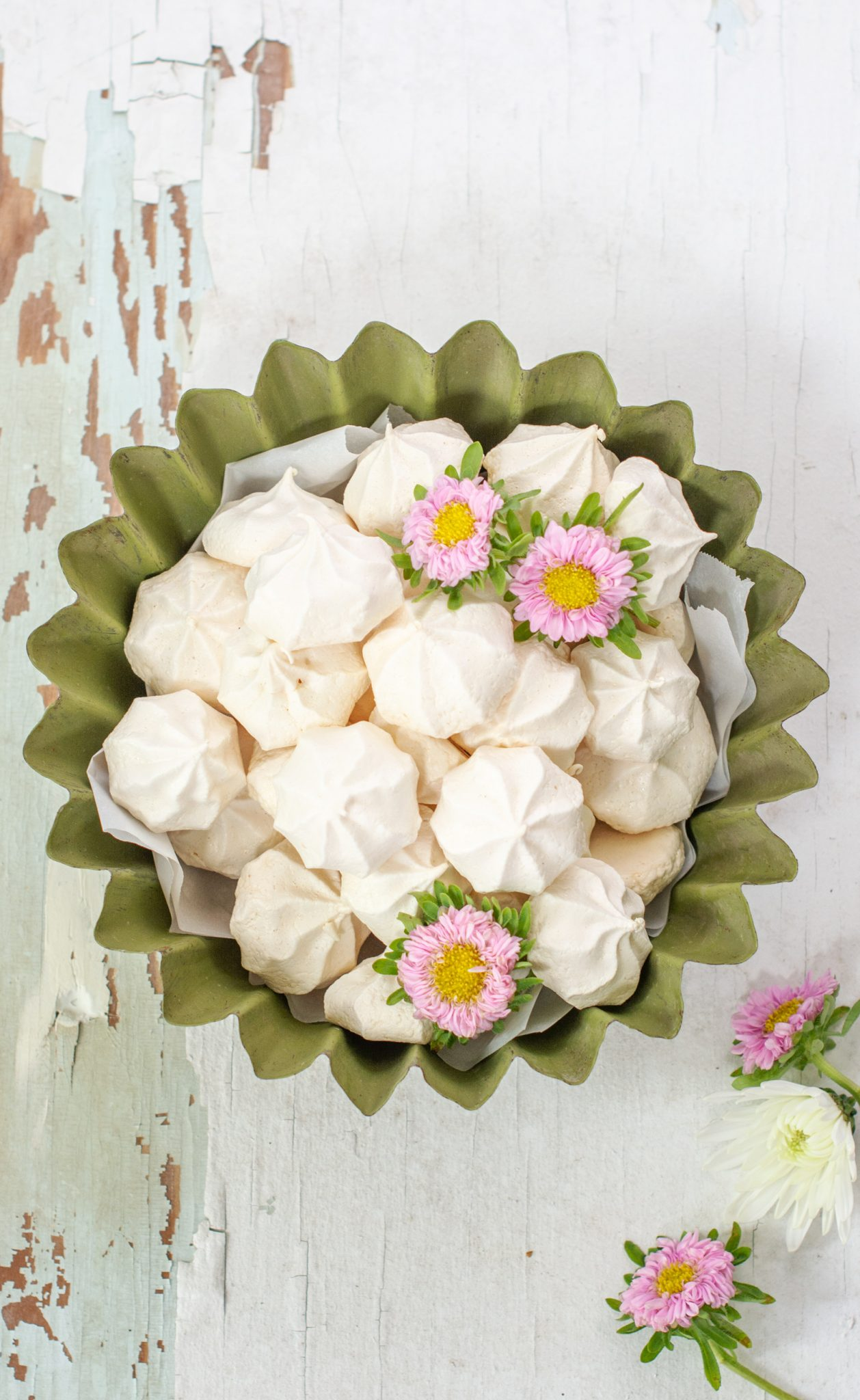 Overhead shot of crunchy meringue cookies in green bowl on white background