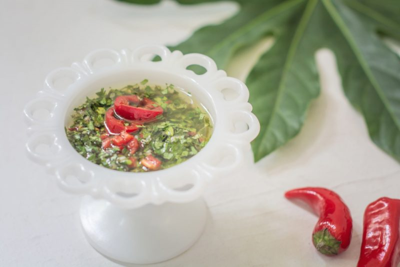 Chimichurri Sauce in a white pedestal bowl with red chili peppers and greenery on white table