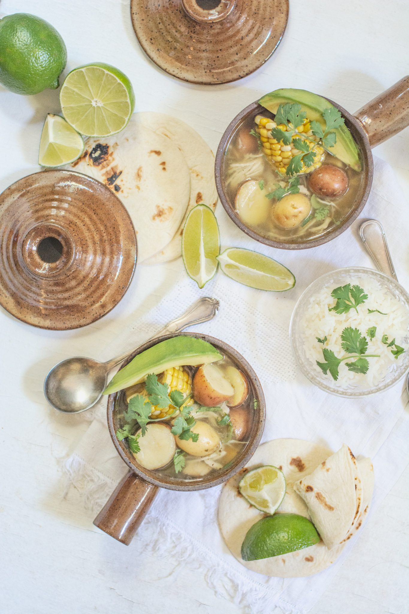 Ajiaco recipe; Colombian Chicken Corn and Potato Stew served on a white table with tortillas, limes and bowls of rice.