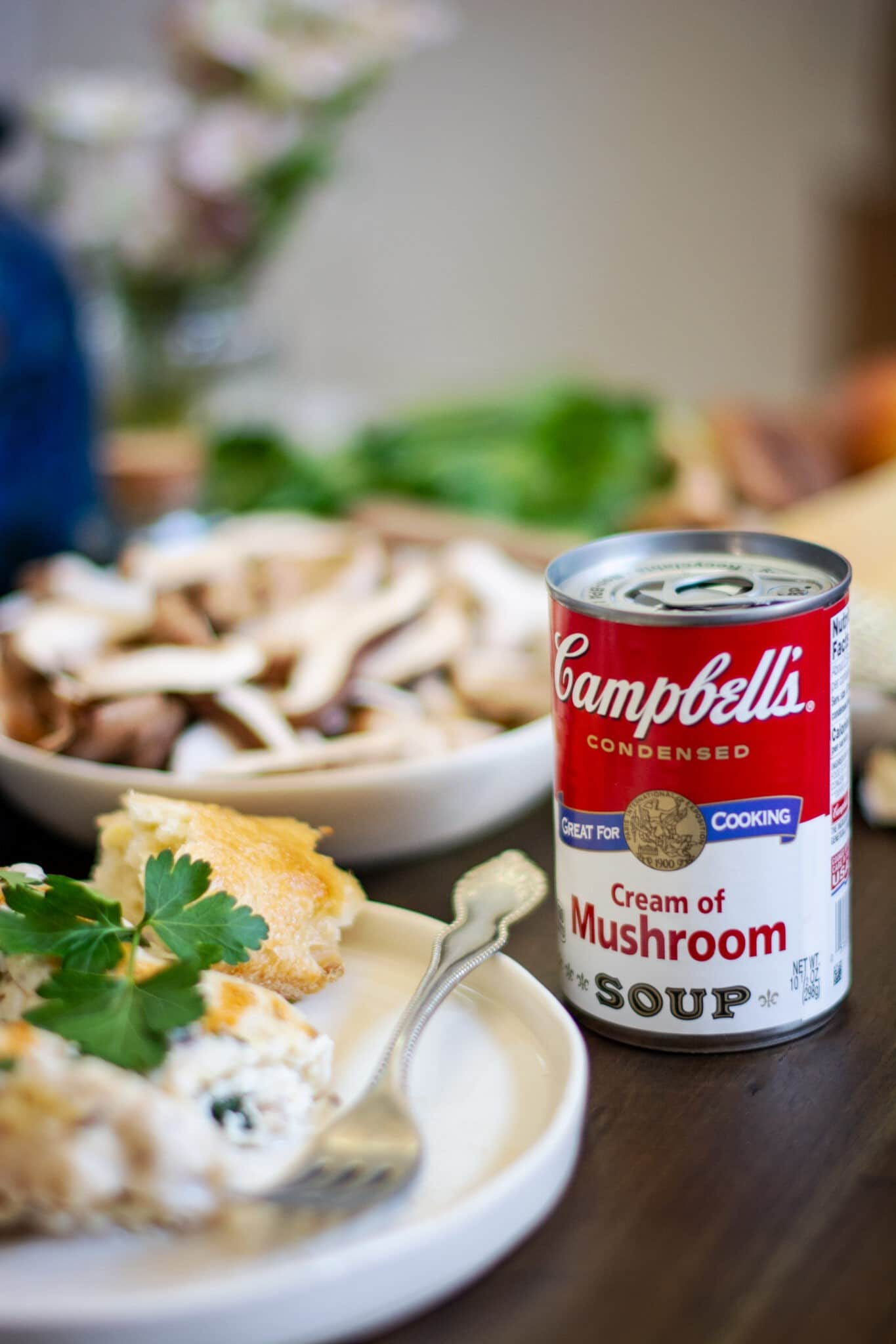Manicotti on white plate with a can of Campbells Cream of Mushroom Soup on wood table